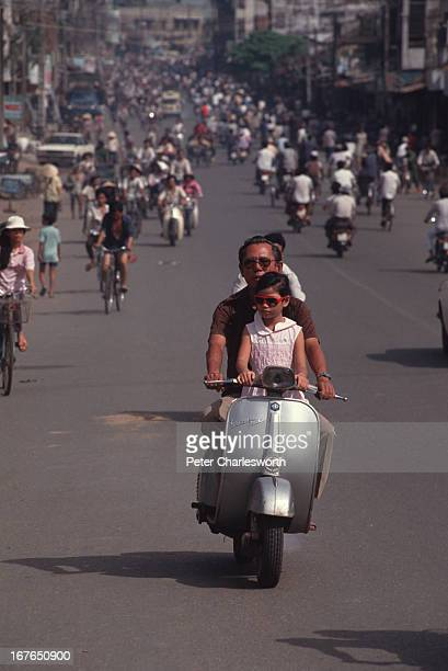 A street scene in Ho Chi Minh City with traffic which mostly consists of bicycles and motorcycles