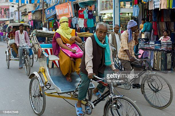 Street scene in holy city of Varanasi, young muslim woman in coloured burkha rides in rickshaw, Benares, Northern India