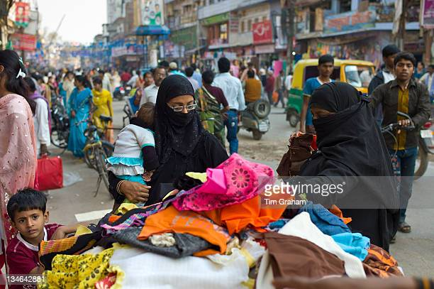Street scene in holy city of Varanasi young muslim women in black burkhas shopping with their children Benares Northern India