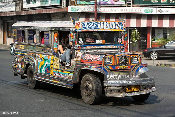 A street scene in Manila the Philippines featuring an flamboyantly decorated jeepney taken on February 08 2013