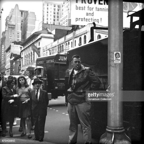 A street scene in NY features people smoking and graffitti that read 'Who is John Galt' on April 25 1962 in New York New York
