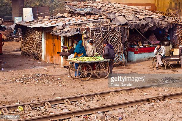 Street scene in rural village along the train tracks. Street vendor with cart, selling fruits. One-story house with roof made of plastic sheets, held...