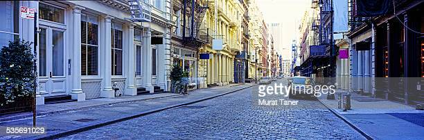 street scene in soho with cast iron buildings - soho new york stock pictures, royalty-free photos & images