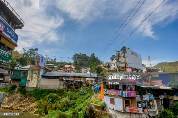 A street scene in the Indian city of Munnar, situated in South India's Kerala region, where people and buildings are visible in the image.