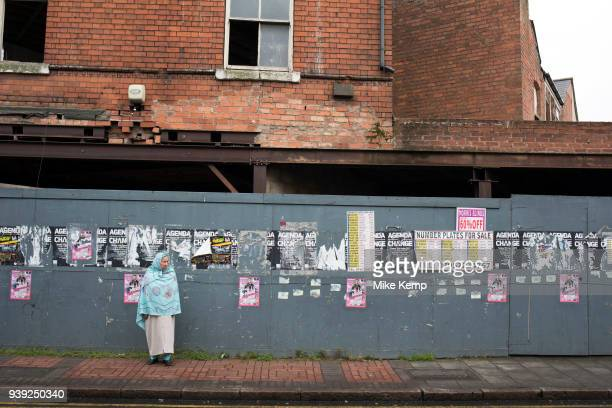 Street scene of everyday life amid boarded up derelict buildings along the Ladypool Road in Sparkbrook Birmingham England United Kingdom This area is...