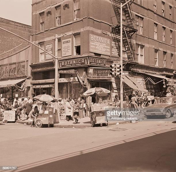 1970s: Street scene of people at small shops in Spanish Harlem in New York.