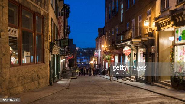 street scene of petit champlain district, in old quebec city, where historical buildings and people walking around can be seen in the image. - old quebec stock pictures, royalty-free photos & images