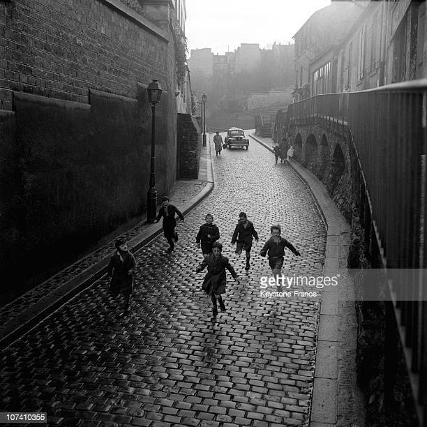 Street Scene On Montmartre A Children Group Rushes In A Sloping Street In 1955