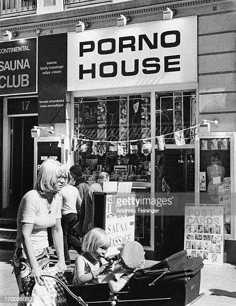 Street scene showing a sex shop and massage parlour titled 'Porno House' New York City 1975