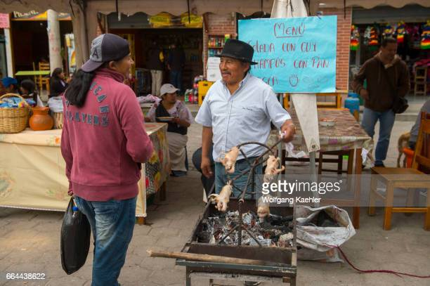 Street scene with a man barbequing guinea pigs in a small village near the town of Otavalo in the highlands of Ecuador near Quito