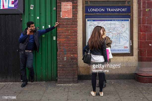 CONTENT] Street scene with a man talking at phone and two girls chatting together by the Camden town underground station in London United Kingdom