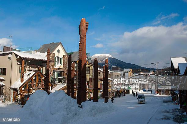 Street scene with carved wooden Ainu poles in Ainu Kotan which is a small Ainu village in Akankohan a street lined by souvenir shops specializing in...