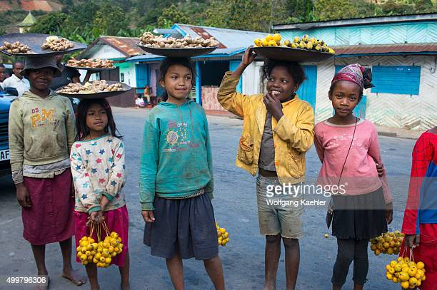 Street scene with children selling fruits and ginger roots in small town in the highlands along highway No 2 east of Antananarivo near Moramanga...