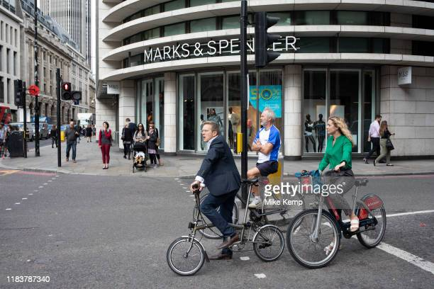 Street scene with different cyclist commuters waiting at the traffic lights in the City of London England United Kingdom Cycling has become a very...