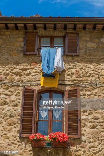 Street scene with flower boxes in front of window in Pienza, Val d'Orcia, Tuscany, Italy.