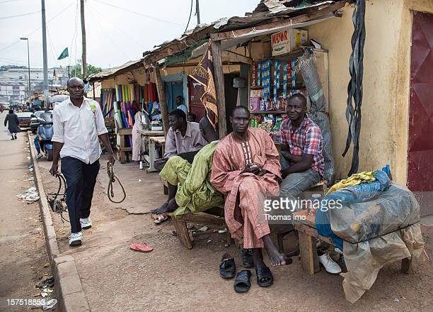 Street scene with locals sitting outside a shop in Yaounde, Cameroon on October 29, 2012.