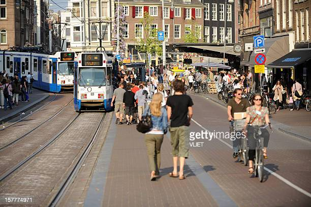 Street scene with trams and crowd of people in Amsterdam