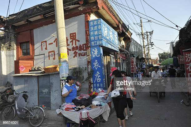 2008 Summer Olympics Aftermath View of former National Stadium volunteer Li Shuqin selling socks fans maps and tshirts from a cart in a back alley of...