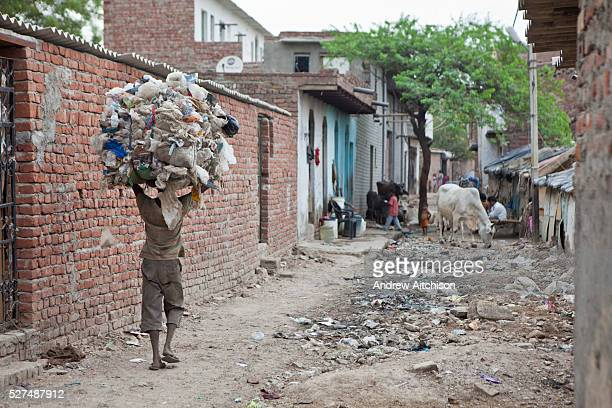Street scenes of Tehkhand Slum Delhi India A man carries a large load of scavenged waste material on his head Many slum dwellers earn a living from...