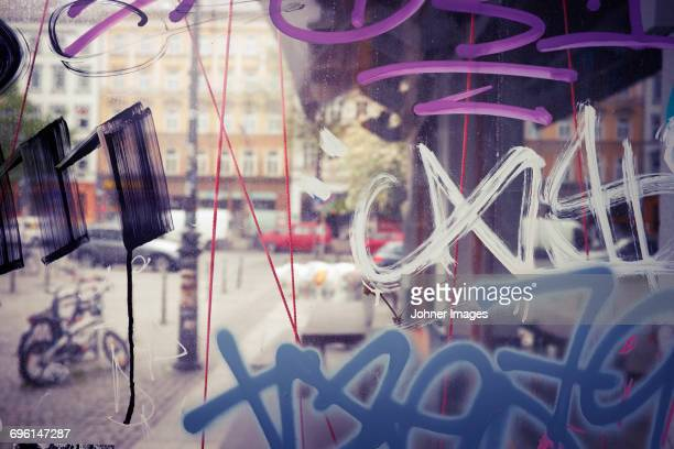 Street seen through window with graffiti