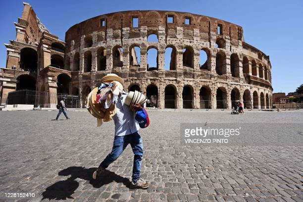 Street seller carries straw hats and caps outside the Colosseum monument on August 22, 2020 in Rome during the COVID-19 infection, caused by the...