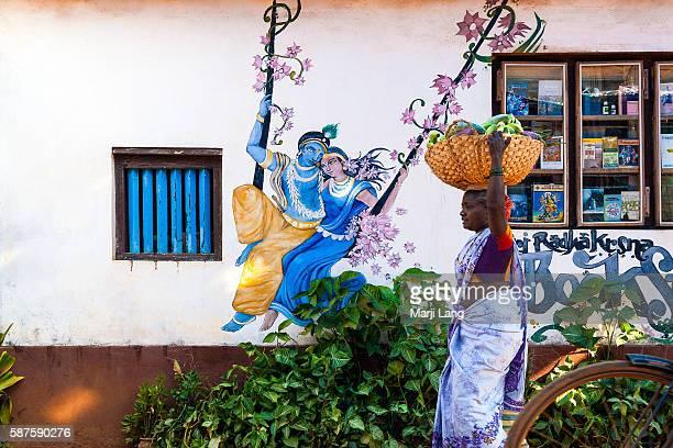 Street seller carrying vegetables by a wall painting of Radha and Krishna on a swing Gokarna Karnataka India