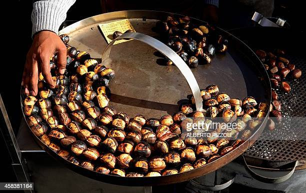 A street seller prepares roasted chestnuts in a touristic place of Rome on November 4 2014 AFP PHOTO / ALBERTO PIZZOLI