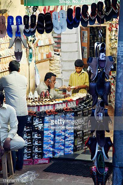 CONTENT] Street shoes shop in Hyderabad India Shop salesperson is talking on mobile phone Small boy counting money Shoes on display hanging on rope...