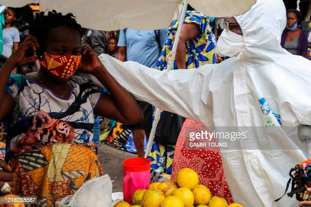 Street shop-keeper is receiving a face mask, as a preventive measure against the spread of the COVID-19 coronavirus, from a Filimbi activist in the...
