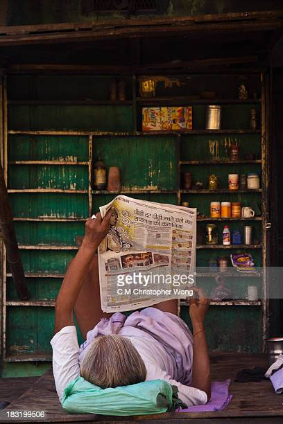 Street side store owner was reading news paper by laying on the table of his store in a hot Summer afternoon.