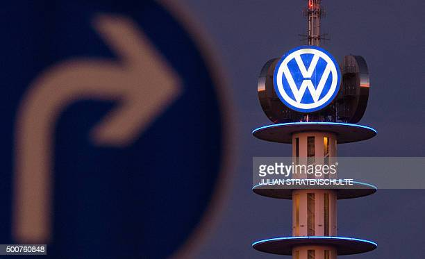 A street sign can be seen in front of the illuminated logo of German car maker Volkswagen on December 10 2015 in Hanover central Germany Embattled...