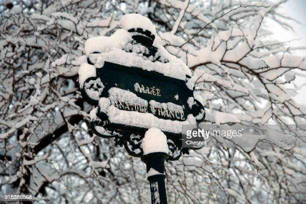A street sign covered by snow is seen in the Champs de Mars garden near the Eiffel Tower on February 7 2018 in Paris France After exceptionally heavy...