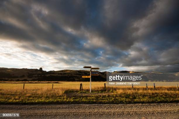 street sign in golden sunrise light with dramatic cloudy sky in background in rural wairarapa - country road stock pictures, royalty-free photos & images