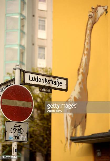 A street sign indicating a street named after the founder of German South West Africa Adolf Luederitz is seen in front of a mural of a giraffe on...