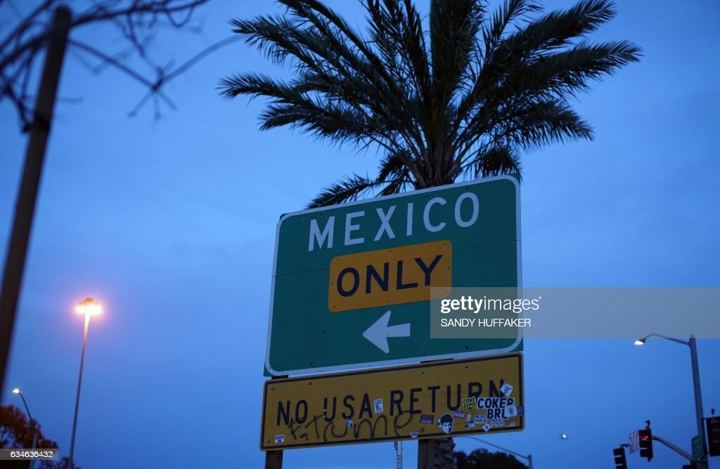 A street sign leading into Mexico atThe United States-Mexico Border wall near the San Ysidro Port of Entry in San Ysidro, California on Friday, February 10, 2017. US Department of Homeland Security (DHS) Secretary John Kelly visited the San Ysidro Port of Entry February 10, 2017 in San Ysidro, California. / AFP / Sandy Huffaker