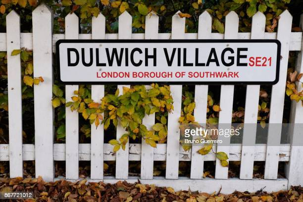 Street sign on wooden fence surrounded by autumn coloured leaves