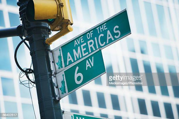 street sign under streetlight for the avenue of the americas and 6th avenue, new york city, ny, usa - sixth avenue stock pictures, royalty-free photos & images