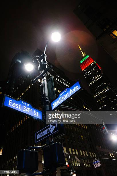 Street signs and Empire State Building at night, New York City, USA