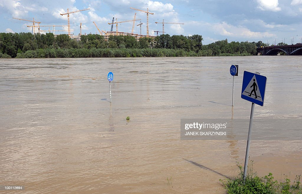 Street signs stand in flood water at Wisla river in Warsaw on May 21, 2010 with the construction site of the national football stadium for EURO 2012 in background. Flash floods caused by days heavy rainfall have hit parts of central Europe, killing at least seven people, disrupting power supplies and forcing thousands of people from their homes. Southern Poland, parts of the Czech Republic and Slovakia and northern Hungary are among the worst affected regions