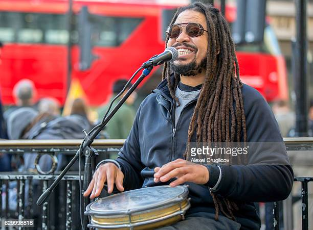 street singer with jembe. united kingdom - reggae stock photos and pictures