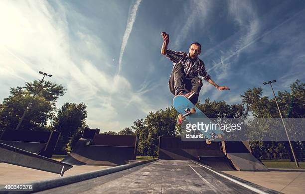 street skateboarder on a skate ramp against the sky. - ollie pictures stock pictures, royalty-free photos & images