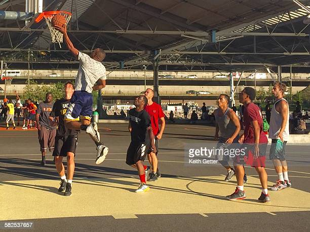 A basketball player soars through the air toward the hoop trying to score during a pickup game on an outside court in Brooklyn NYC