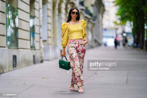 Street style photo session with Gabriella Berdugo wearing Kenzo sunglasses, a yellow ruffled top with puff sleeves and shoulder pads from Avavav,...