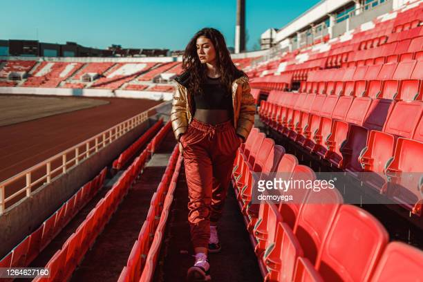 street styled young woman in an empty sports stadium - audience free event stock pictures, royalty-free photos & images