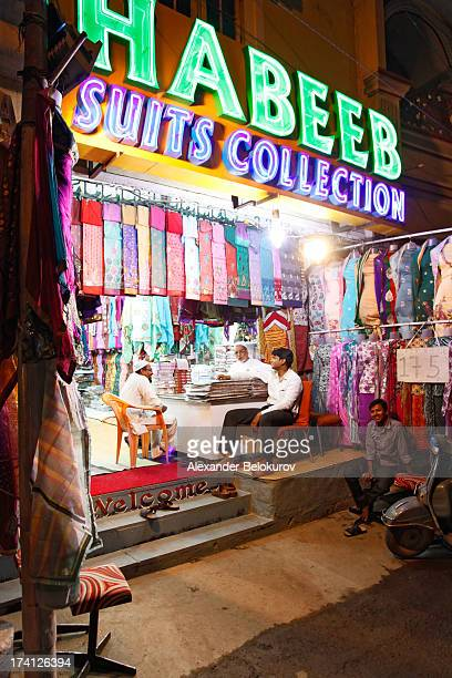 Street suits and dress shop in Hyderabad, India. Several men are sitting inside the shop and discussing. Possible Arab origin. Colorful dresses are...