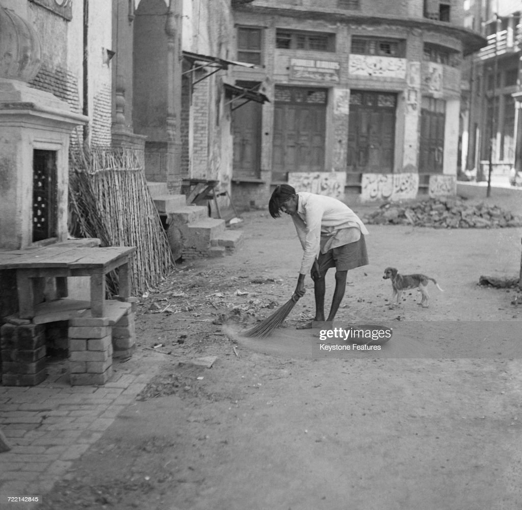 A street sweeper at work after communal riots in Amritsar Punjab during the Partition of British India March 1947 The man has permission to work but..