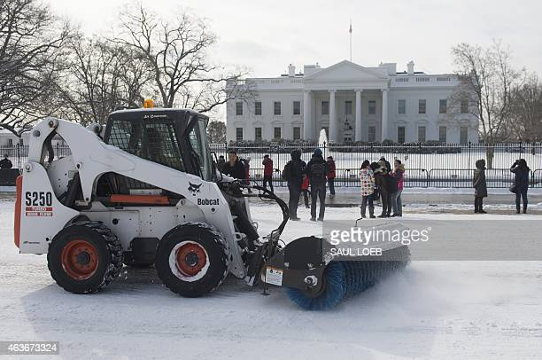 A street sweeper cleans snow off the road in front of the White House in Washington DC February 17 following an overnight snow storm AFP PHOTO / SAUL...