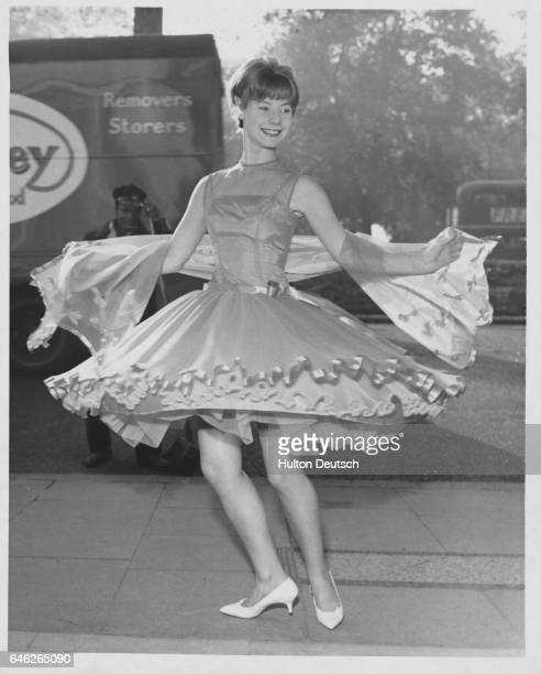 A street sweeper looks on as 17yearold Ingrid Young models a party dress outside London's Dorchester Hotel The dress comprises a highnecked slim...