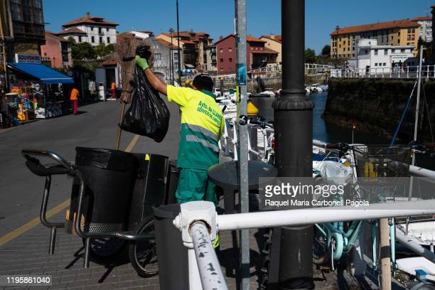 Street sweeper man with cart cleaning the streets of the port