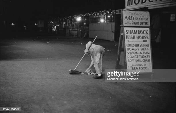 Street sweeper next to a sign advertising the Shamrock Irish House at Coney Island in New York City, circa 1955. Marty and his Singing Waiters are...